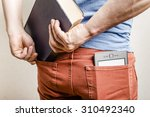Small photo of in the back pocket of jeans is an e-book, a man tries to shove in a second pocket thick old paper book