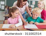 smiling female teacher helping... | Shutterstock . vector #311002514