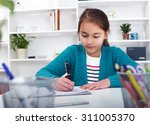 beautiful girl working on her... | Shutterstock . vector #311005370