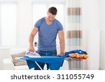 young happy man ironing clothes ... | Shutterstock . vector #311055749