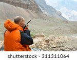 Small photo of Man Talking on Radio. Mountain Rescue Officer Holding Radio Walkies Talkie and Severe Mountain Landscape Background