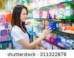 young female pharmacist picking ... | Shutterstock . vector #311322878