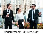 Stock photo quick briefing before meeting three cheerful young business people talking to each other while 311390639