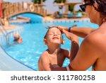mother putting sunscreen on her ... | Shutterstock . vector #311780258