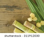 Small photo of Fresh sugarcane cut into pieces on a wooden table with leaves and cane.