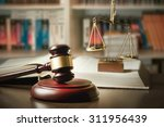 Stock photo judge gavel and scale in court library with lot of books in background 311956439