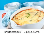 Stock photo zucchini lasagna with cheese tomatoes in white bowl on blue background 312164696
