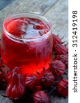 Small photo of Closeup of roselle drink and fruit over wooden surface