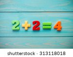 Small photo of Simple mathematical addition on a wooden surface
