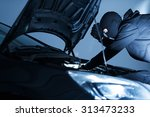 Robber Disabling Car Alarm. Car Robber Looking To Disarm Car Security Systems Under the Car Hood.  - stock photo