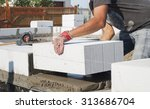 Small photo of builder puts on grout aerated concrete block