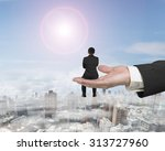 Small photo of Rear view of small businessman sitting on big male hand palm open, with sunny sky cityscape background.