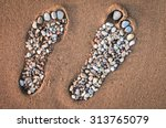 Small photo of Bare feet made of pebble on the sandy beach
