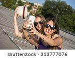 two young girls with a mobile... | Shutterstock . vector #313777076