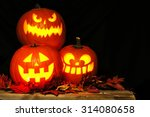 Stock photo stacked halloween jack o lanterns illuminated at night with old wood and autumn leaves 314080658
