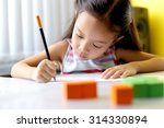 a little girl concentrates her... | Shutterstock . vector #314330894