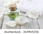 Stock photo bottle of green essential oil white rose petals and soft towel on a wooden background 314965256