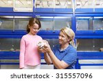 Stock photo sales assistant showing girl guinea pig in pet store 315557096