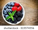 various berries in a white bowl ... | Shutterstock . vector #315574556