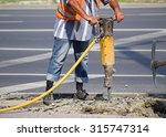 Small photo of Man works with an air hammer at the road construction
