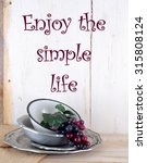 Small photo of Rustic scene of purple grapes in a worn vintage enamel bowl stacked on old pewter dishes sitting on a wood table in front of a white-washed wood background with burlap tucked underneath. Message added