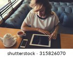 Small photo of Young attractive woman concentrated reading electronic book on her digital tablet, caucasian female browsing website pages on touch pad while breakfast in modern coffee shop, people using technology