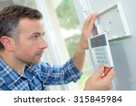 Small photo of Electrician fitting an intrusion alarm