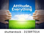 "Small photo of Motivational quotes ""Attitude is Everything"" . Hands opening a wooden door then found a texts floating among new world as green grass field, Blue sky and the Sunrise."