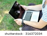 young man with laptop outdoors | Shutterstock . vector #316372034