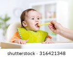 mother feeding baby girl at... | Shutterstock . vector #316421348