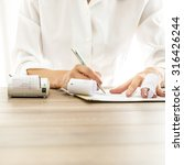 Small photo of Front view of female bank employee in elegant white blouse writing something on receipts with documents and adding machine on her wooden desk.