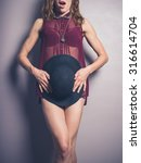 Small photo of A seductive young woman wearing see through lingerie is covering her modesty with a hat