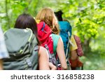 Small photo of adventure, travel, tourism, hike and people concept - close up of friends walking with backpacks in woods from back