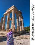 Small photo of Self selfie shot of a smiling young woman in front of the ruins of the Temple of Zeus, Archaeological Site of Ancient Nemea, Peloponnese, Greece.