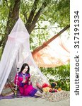 Small photo of Beautiful young dark-haired woman in a colorful Arabic garb sitting under a white tent, smoke hookah, oriental style