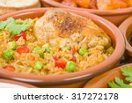 Arroz Con Pollo - Chicken and rice cooked with sofrito and beer. Surrounded by other tapas dishes.