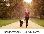 Stock photo full length shot of a healthy young woman jogging in the park with her black pet dog 317321696