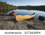 A Yellow Canoe Rests On A Rock...