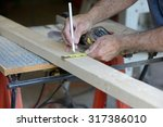 worker measuring wood to cut on ...