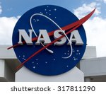 NASA sign at Cape Canaveral, Kennedy Space Center with blue cloudy sky background. Elements of this image furnished by NASA.