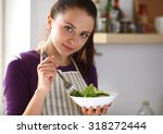 a young woman eating salad in...