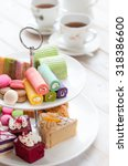 Small photo of cakes and macaroons on two tiered tray with teapot and cup background. Afternoon tea