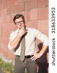 Small photo of Hipster businessman with look of verjuice touching his face outdoors. Handsome man in glasses keeping his hand on hip near red columns wall.
