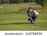Female Golfer Lining Up A Putt...