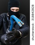 Small photo of Felony concept. Robber or aggressor masked with black balaclava is attacking with crowbar.