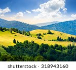 bald hills with meadow and some trees among mountains with coniferous forest at sunrise - stock photo