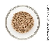 Small photo of Top view of Organic Ajwain (Trachyspermum ammi) half filled in glass bowl isolated on white background.