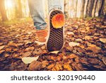 Small photo of Feet sneakers walking on fall leaves Outdoor with Autumn season nature on background Lifestyle Fashion trendy style