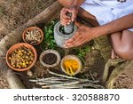 Small photo of A young man preparing ayurvedic medicine in the traditional manner.
