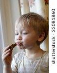 the little boy eats a bread at...   Shutterstock . vector #32081860